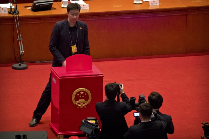 A staff member stands in front of a ballot box on the rostrum before a plenary session of China's National People's Congress (NPC) at the Great Hall of the People in Beijing, Sunday, March 11, 2018. China's top legislative body is expected to approve an amendment too China's constitution on Sunday that will abolish term limits on the presidency and enable Chinese President Xi Jinping to rule indefinitely. (AP Photo/Mark Schiefelbein)