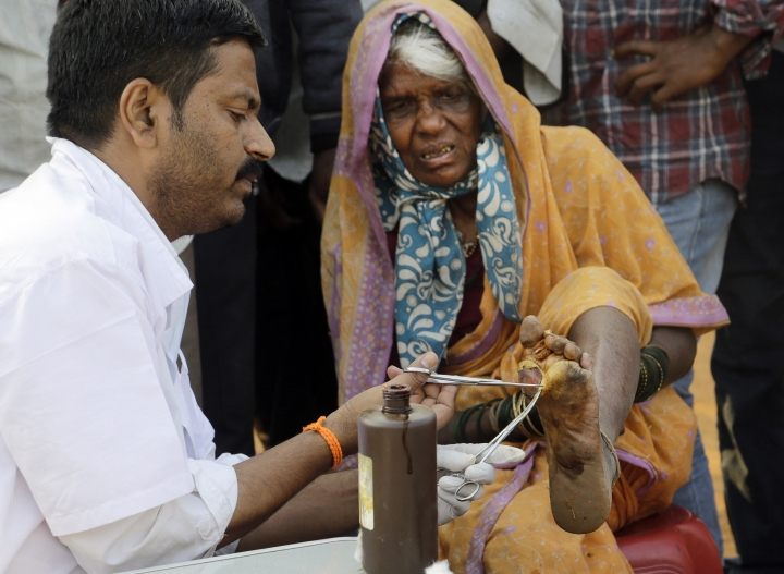 A doctor cleans the wound of a woman farmer at the end of her six day long march on foot, in Mumbai, India, Monday, March 12, 2018. Tens of thousands of farmers from across western India have arrived in Mumbai demanding, among other things, a waiver of farm loans and fair prices for their produce as India's agriculture sector struggles amid years of declining earnings. The farmers reached India's business capital Monday after marching on foot for up to six days and plan to surround the state legislature of the western state of Maharashtra in Mumbai. (AP Photo/Rajanish Kakade)