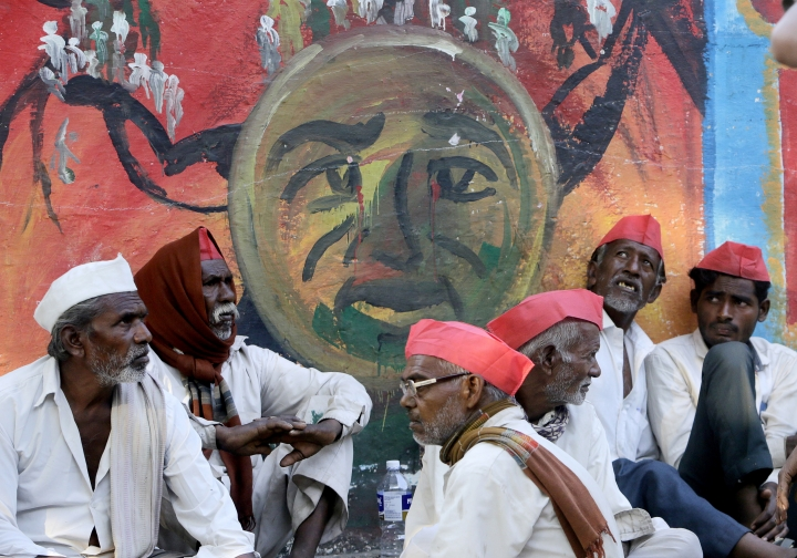 Indian farmers sit in front of a graffiti at the end of their six day long march on foot, in Mumbai, India, Monday, March 12, 2018. Tens of thousands of farmers from across western India have arrived in Mumbai demanding, among other things, a waiver of farm loans and fair prices for their produce as India's agriculture sector struggles amid years of declining earnings. The farmers reached India's business capital Monday after marching on foot for up to six days and plan to surround the state legislature of the western state of Maharashtra in Mumbai. (AP Photo/Rajanish Kakade)
