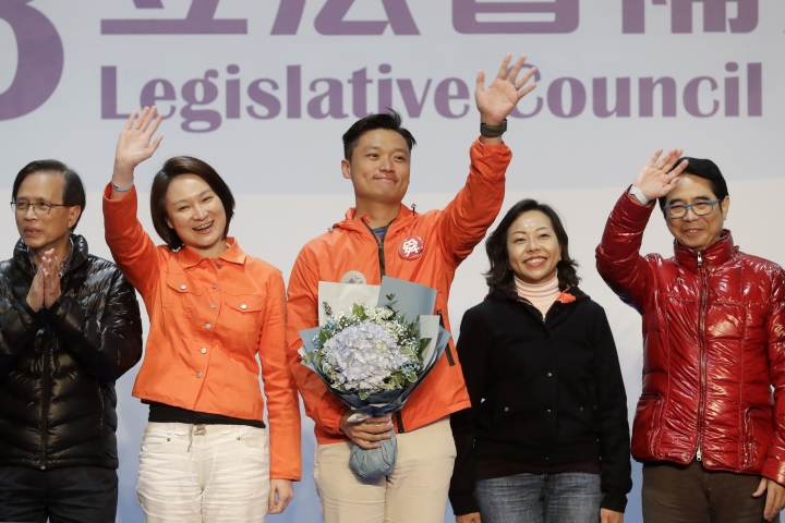 Hong Kong pro-Beijing by-election candidate Vincent Cheng Wing-shun, center, celebrates with his supporters after winning a seat at the legislative council by-elections in Hong Kong, Monday, March 12, 2018. Hong Kong pro-democracy candidates won back only two of four seats in a crucial by-election in the semiautonomous Chinese region, final results showed Monday. (AP Photo/Kin Cheung)