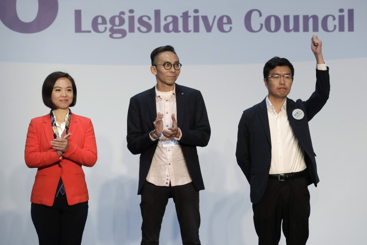 Hong Kong pro-democracy by-election candidate Au Nok-hin, right, celebrates next to his competitor pro-Beijing candidate Judy Chan, left, after winning a seat at the legislative council by-elections in Hong Kong, Monday, March 12, 2018. (AP Photo/Kin Cheung)