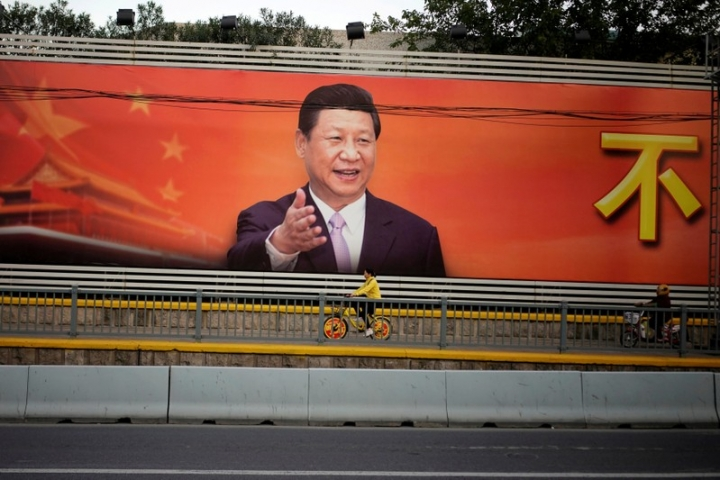 FILE PHOTO: A poster with a portrait of Chinese President Xi Jinping is displayed along a street in Shanghai, China, October 24, 2017. REUTERS/Aly Song/File Photo