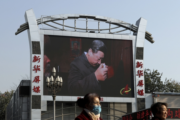 In this Nov. 16, 2017, photo, women walk by a TV screen showing a documentary footage of Chinese President Xi Jinping visiting a villager's house with a picture of late communist leader Mao Zedong, at the Beijing railway station in Beijing. Many Western scholars who studied China believed that the opening to the outside world engineered by reformer Deng Xiaoping in the early 1980s would pave the way for corresponding political freedoms. That vision has been categorically shattered under President Xi Jinping, who many once thought would be the next great reformer. In just five years, Xi has consolidated more power than any Chinese leader since Mao Zedong and is now primed to rule as president-for-life. (AP Photo/Andy Wong)