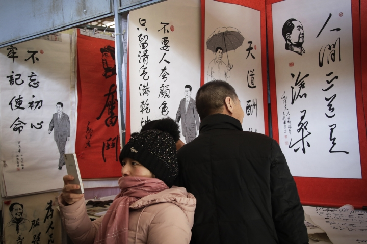 In this March 1, 2018, photo, a women takes a picture as a couple looks at posters featuring drawings of Chinese President Xi Jinping and late communist leader Mao Zedong with their quotes, on display for sale at a market in Beijing. Many Western scholars who studied China believed that the opening to the outside world engineered by reformer Deng Xiaoping in the early 1980s would pave the way for corresponding political freedoms. That vision has been categorically shattered under President Xi Jinping, who many once thought would be the next great reformer. In just five years, Xi has consolidated more power than any Chinese leader since Mao Zedong and is now primed to rule as president-for-life. (AP Photo/Andy Wong)