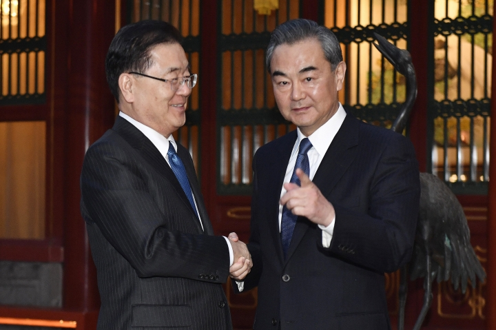 South Korean national security director Chung Eui-yong, left, shakes hands with Chinese Foreign Minister Wang Yi before their meeting at Diaoyutai State Guesthouse in Beijing, Monday, March 12, 2018. (Kenzaburo Fukuhara/Pool Photo via AP)