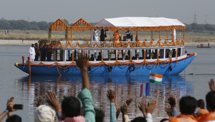 French President Emmanuel Macron, center and Indian Prime Minister Narendra Modi, center left, wave as they take a boat ride in the River Ganges in Varanasi, India, Monday, March 12, 2018. Macron arrived in India on Friday on a four-day visit. Also seen is India's northern Uttar Pradesh state Chief Minister Yogi Adityanath, center, right. (AP Photo/Rajesh Kumar Singh)