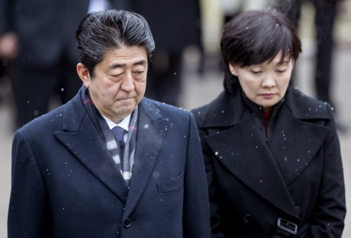 FILE - In this Jan. 14, 2018, file photo, Japanese Prime Minister Shinzo Abe, left, and his wife Akie Abe take part in a wreath laying ceremony at the Antakalnis Memorial Cemetery in Vilnius, Lithuania. Japan's Finance Ministry acknowledged doctoring documents on Monday, March 12, 2018 in a widening scandal linked to first lady Akie that has rattled his government. The doctored documents related to the 2016 sale of state land to a school operator in Osaka at one-seventh of its appraised price with the alleged involvement of Akie Abe, who supported the school's ultra-nationalistic education policy. (AP Photo/Liusjenas Kulbis, File)