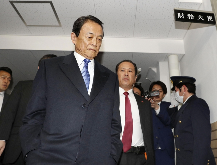 """Japanese Finance Minister Taro Aso arrives at his room of Finance Ministry in Tokyo Monday, March 12, 2018. Aso has acknowledged doctoring documents in a widening scandal linked to Prime Minister Shinzo Abe's wife that has rattled his government. Aso said Monday that an investigation by the ministry and prosecutors has found 14 instances of alterations. The plate at right top reads: """"Finance minister."""" (Takuya Inaba/Kyodo News via AP)"""