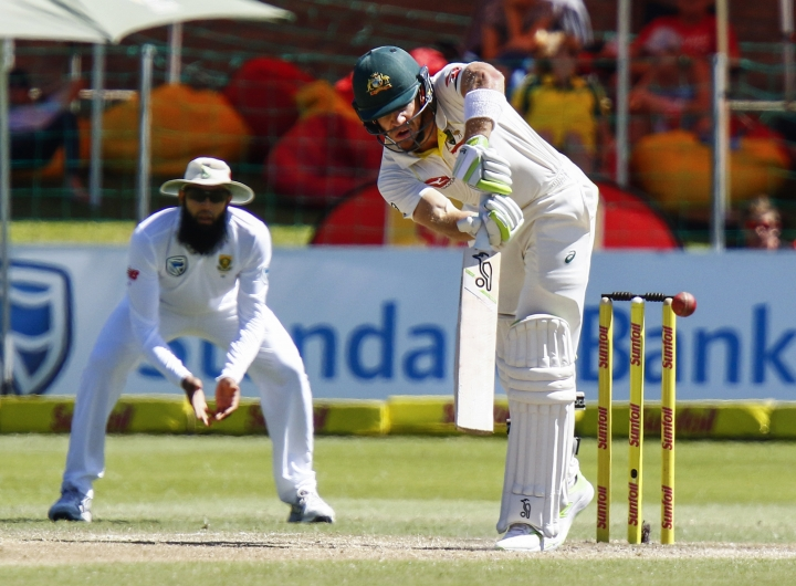 Australia's Tim Paine bats, as South Africa's wicket keeper Hashim Amla fields, on the fourth day of the second cricket test between South Africa and Australia at St. George's Park in Port Elizabeth, South Africa, Monday, March 12, 2018. (AP Photo/Michael Sheehan)