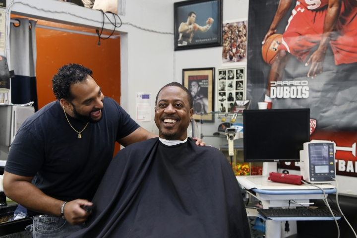 In this Sunday, March 11, 2018, photo, Barber Eric Muhammad, owner of A New You Barbershop, left, jokes with regular customer Marc M. Sims before measuring his blood pressure in Inglewood, Calif. Black male customers at dozens of Los Angeles area barbershops reduced one of their biggest health risks through a novel project that paired barbers and pharmacists to test and treat customers. (AP Photo/Damian Dovarganes)