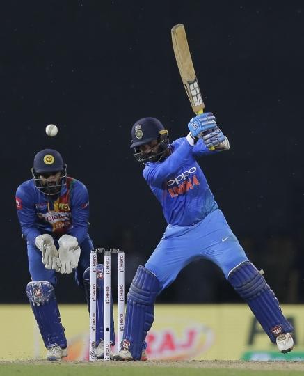 India's Dinesh Karthik plays a shot as Sri Lanka's Kusal Perera watches during their Twenty20 cricket match in Nidahas triangular series in Colombo, Sri Lanka, Monday, March 12, 2018. (AP Photo/Eranga Jayawardena)