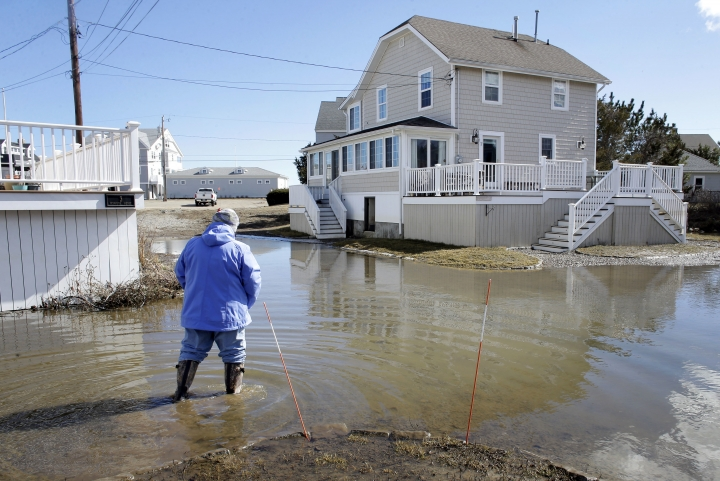 A resident of Duxbury, Mass., views flooding near her home, Sunday, March 11, 2018, in Duxbury. The Northeast is bracing for its third nor'easter in fewer than two weeks. The National Weather Service reports Sunday that a southern storm is expected to make its way up the coast causing more snowfall. (AP Photo/Steven Senne)