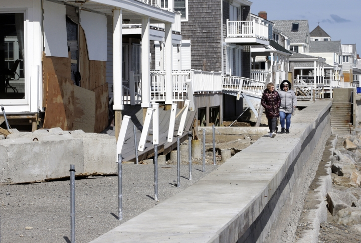 Maureen Niland, of Marshfield, Mass., left, and Kim Varghese, of Plymouth, Mass., right, walk along a seawall near damaged beachfront homes, Sunday, March 11, 2018, in Marshfield. The Northeast is bracing for its third nor'easter in fewer than two weeks. The National Weather Service reports Sunday that a southern storm is expected to make its way up the coast causing more snowfall. (AP Photo/Steven Senne)