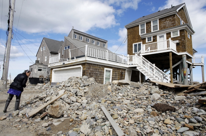 A passerby pauses near a pile of rocks, sand and debris near beachfront homes, Sunday, March 11, 2018, in Marshfield, Mass. The Northeast is bracing for its third nor'easter in fewer than two weeks. The National Weather Service reports Sunday that a southern storm is expected to make its way up the coast causing more snowfall. (AP Photo/Steven Senne)