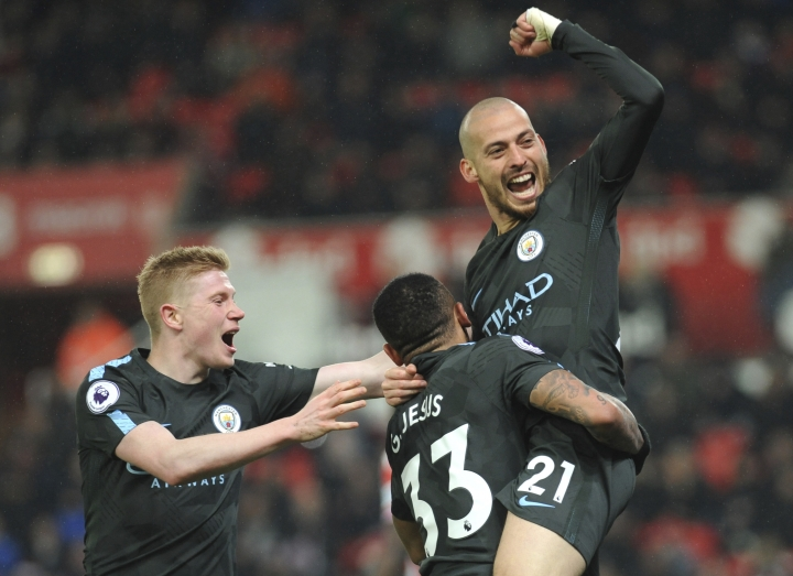 Manchester City's David Silva, right, celebrates scoring his second goal during the English Premier League soccer match between Stoke City and Manchester City at the Bet 365 Stadium in Stoke on Trent, England, Monday, March 12, 2018. (AP Photo/Rui Vieira)