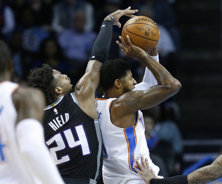 Oklahoma City Thunder forward Paul George, right, goes to the basket in front of Sacramento Kings guard Buddy Hield (24) in the first half of an NBA basketball game in Oklahoma City, Monday, March 12, 2018. (AP Photo/Sue Ogrocki)