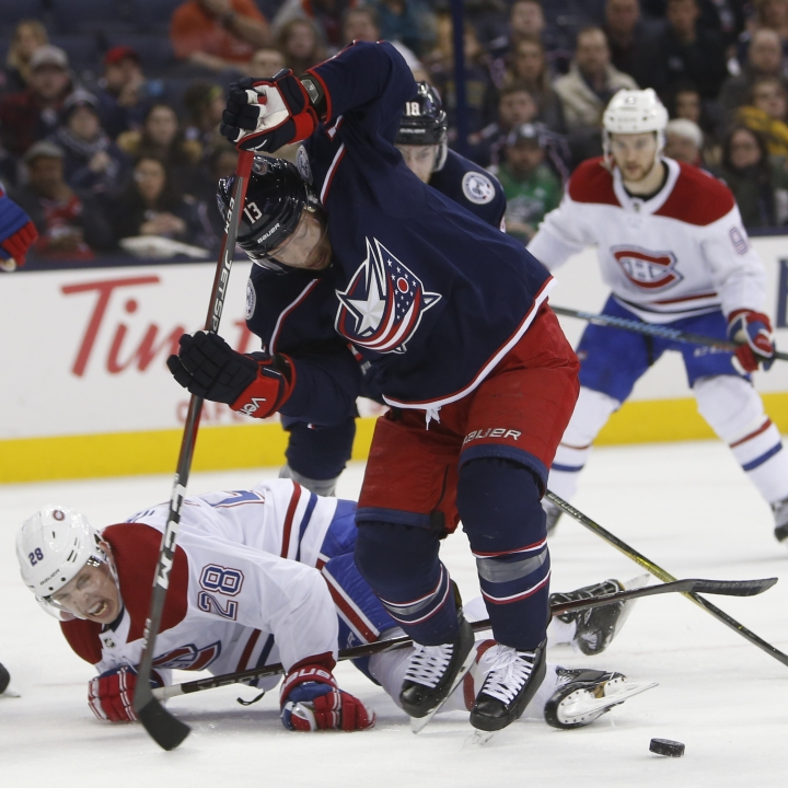 Columbus Blue Jackets' Cam Atkinson, front right, takes the puck away from Montreal Canadiens' Mike Reilly during the second period of an NHL hockey game Monday, March 12, 2018, in Columbus, Ohio. (AP Photo/Jay LaPrete)