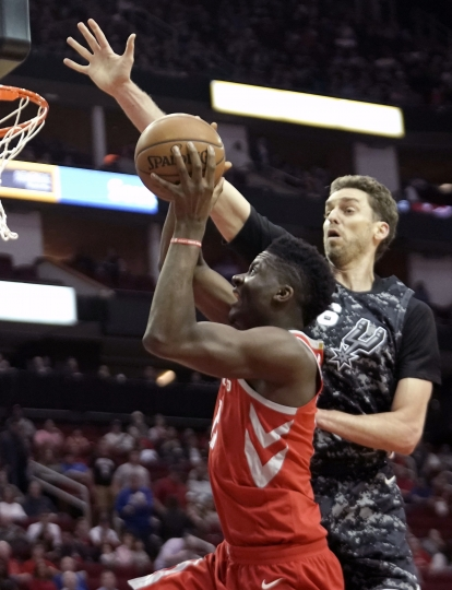 Houston Rockets' Clint Capela, left, is fouled by San Antonio Spurs' Pau Gasol during the first half of an NBA basketball game Monday, March 12, 2018, in Houston. (AP Photo/David J. Phillip)