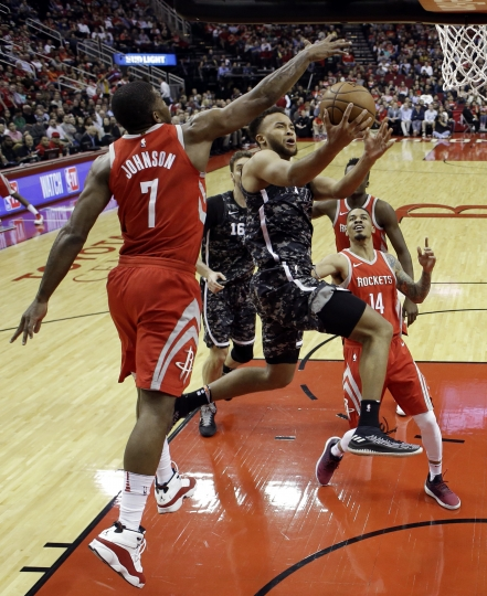 San Antonio Spurs' Kyle Anderson, center, goes up to shoot as Houston Rockets' Joe Johnson (7) defends during the first half of an NBA basketball game Monday, March 12, 2018, in Houston. (AP Photo/David J. Phillip)