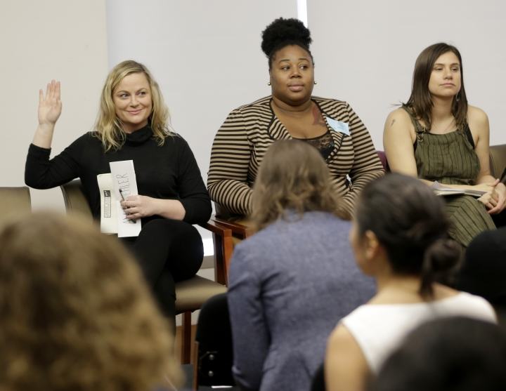In this Feb. 20, 2018, Amy Poehler, left, raises her hand to indicate that she once worked as a waitress while Shanita Thomas, center, and Gemma Rossi listen during a discussion about subminimum wage workers that depend on tips for their living in New York. Poehler was there to support tipped workers, like Thomas and Rossi, who would like to see one fair wage for all workers. (AP Photo/Seth Wenig)