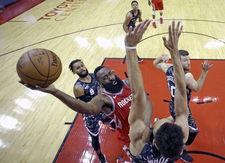 Houston Rockets' James Harden, center, shoots as San Antonio Spurs' Derrick White, bottom, defends during the second half of an NBA basketball game Monday, March 12, 2018, in Houston. (AP Photo/David J. Phillip)
