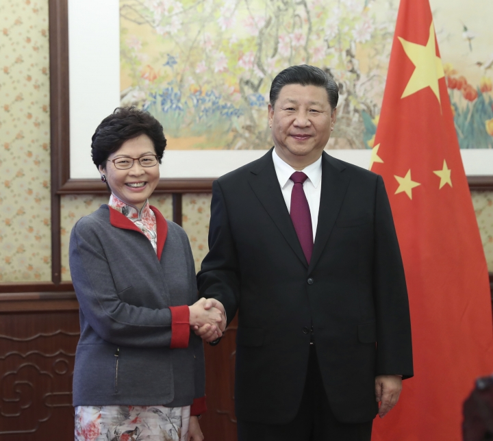 FILE - In this Dec. 15, 2017, file photo released by China's Xinhua News Agency, Hong Kong Chief Executive Carrie Lam, left, poses with Chinese President Xi Jinping for a photo during a meeting in Beijing. China's move to scrap term limits and allow Xi Jinping to serve as president indefinitely puts him on track to deal with some of the country's weightiest long-term sovereignty challenges, especially the fates of Hong Kong and Taiwan. (Xie Huanchi/Xinhua via AP, File)
