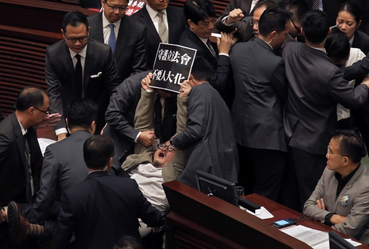 "FILE - In this Dec. 15, 2017, file photo, pro-democracy lawmaker Shiu Ka-chun holds up a placard reading ""Don't be like China's People's Congress"" while being carried away by security guards at the legislative council in Hong Kong, after Hong Kong's pro-Beijing establishment lawmakers passed an amendment aimed at stopping filibustering tactics frequently despite furious opposition from their pro-democracy rivals. China's move to scrap term limits and allow Xi Jinping to serve as president indefinitely puts him on track to deal with some of the country's weightiest long-term sovereignty challenges, especially the fates of Hong Kong and Taiwan. (AP Photo/Vincent Yu, File)"