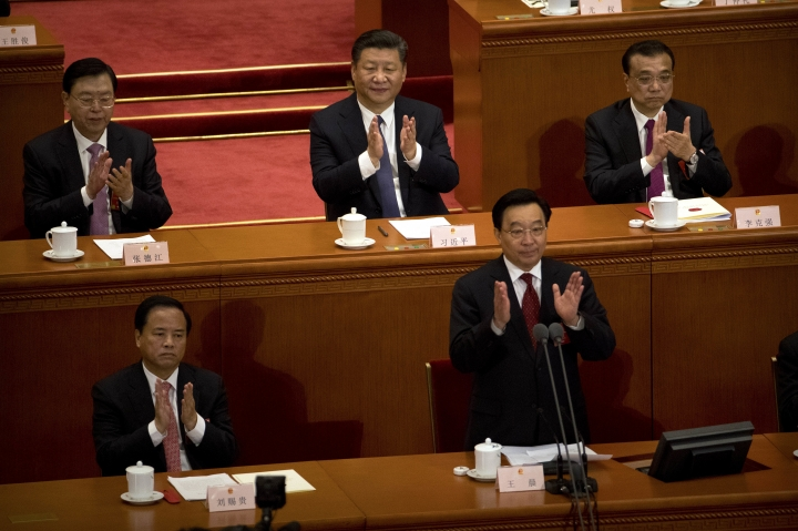 In this Sunday, March 11, 2018, photo, Chinese President Xi Jinping, top center, applauds after hearing the results of a vote on a constitutional amendment during a plenary session of China's National People's Congress (NPC) at the Great Hall of the People in Beijing. China's move to scrap term limits and allow Xi to serve as president indefinitely puts him on track to deal with some of the country's weightiest long-term sovereignty challenges, especially the fates of Hong Kong and Taiwan. (AP Photo/Mark Schiefelbein)