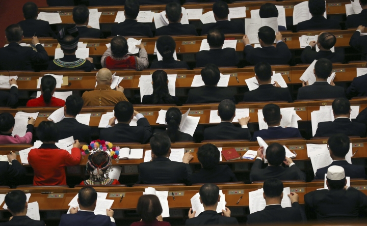Delegates read the work reports during a plenary session of China's National People's Congress (NPC) at the Great Hall of the People in Beijing, Tuesday, March 13, 2018. Chinese President Xi Jinping's anti-corruption campaign stands to gain a major boost as the ceremonial legislature moves to establish a powerful new agency with authority over vast numbers of workers in the public sector. (AP Photo/Aijaz Rahi)