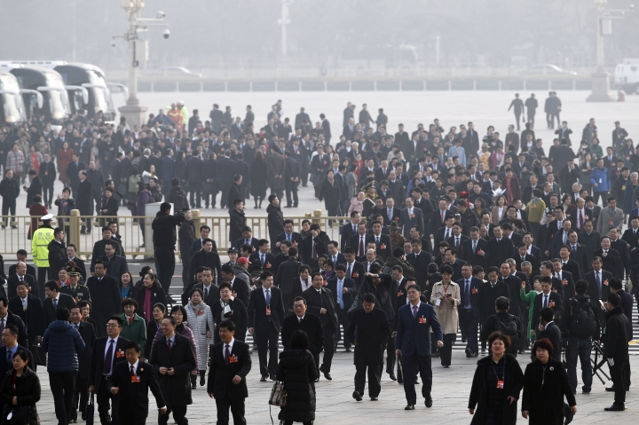 Delegates walk on Tiananmen Square shrouded with pollution haze as they arrive to attend a plenary session of China's National People's Congress (NPC) at the Great Hall of the People in Beijing, Tuesday, March 13, 2018. Chinese President Xi Jinping's anti-corruption campaign stands to gain a major boost as the ceremonial legislature moves to establish a powerful new agency with authority over vast numbers of workers in the public sector. (AP Photo/Andy Wong)