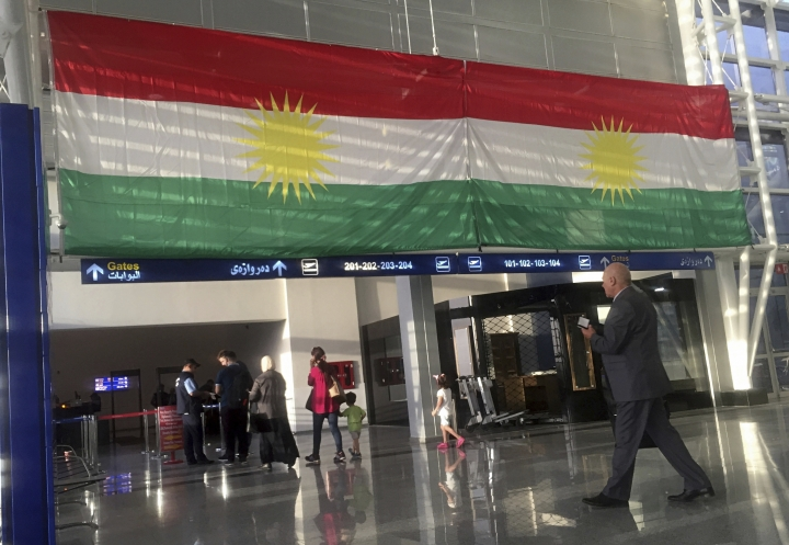 FILE - In this Sept. 27, 2017 file photo, a Kurdish flag hangs in the Irbil International Airport, Iraq. Iraqi Prime Minister Haider al-Abadi said Tuesday, March 13, 2018, that he is reopening airports in Iraq's Kurdish region to international flights after federal authority was restored at the hubs. The announcement comes some six months after the airports were initially shut to international flights following a controversial referendum vote in northern Ira's self-ruled Kurdish region on independence from Baghdad. (AP Photo/Khalid Mohammed, File)