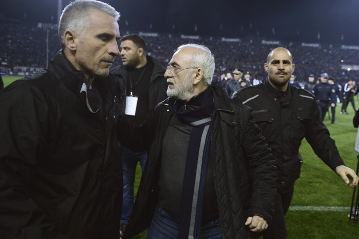 In this photo taken on Sunday, March 11, 2018, PAOK owner, businessman Ivan Savvidis, center, escorted by his bodyguards leaves the pitch during a Greek League soccer match between PAOK and AEK Athens in the northern Greek city of Thessaloniki. A disputed goal at the end of the Greek league match led to a pitch invasion by Savvidis, who appeared to be carrying a gun. (AP Photo)