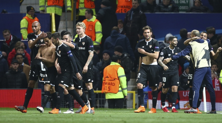 Sevilla's Wissam Ben Yedder, second left puts his shirt back on as he celebrates with teammates after scoring his sides second goal during the Champions League round of 16 second leg soccer match between Manchester United and Sevilla, at Old Trafford in Manchester, England, Tuesday, March 13, 2018. (AP Photo/Dave Thompson)