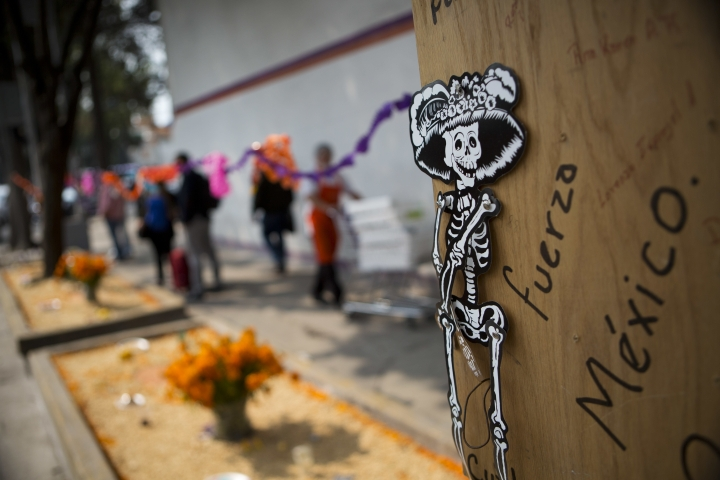 """FILE - In this Oct. 31, 2017 file photo, the Spanish phrase """"Be strong Mexico!"""" is written next to a skeleton figure at a small altar across the street from the remains of Alvaro Obregon 286, where many were killed when the seven-story office building collapsed in the Sept. earthquake in Mexico City. The city government is taking ownership of the lot where the building collapsed in September's deadly earthquake, clearing the way for a planned park memorializing victims of the disaster. Forty-nine people died in the building when it collapsed Sept. 19. (AP Photo/Rebecca Blackwell, File)"""