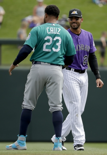 Seattle Mariners designated hitter Nelson Cruz, left, and Colorado Rockies left fielder Ian Desmond chat before a spring training baseball game in Scottsdale, Ariz., Tuesday, March 13, 2018. (AP Photo/Chris Carlson)