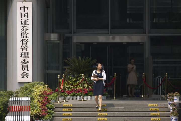 In this July 9, 2015, photo, a woman walks out of the China Securities Regulatory Commission at the Financial Street in Beijing. Chinese securities regulators have imposed a record $870 million fine on a company that manipulated share prices in the latest scandal to roil the country's markets. Regulators said on Wednesday, March 14, 2018 the company in the southeastern city of Xiamen used 300 trading accounts to manipulate prices of shares in smaller banks and other companies. (AP Photo/Andy Wong)