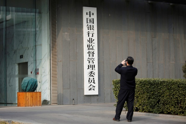 A man takes pictures of a sign of China Banking Regulatory Commission (CBRC) at its office in Beijing, China March 13, 2018.  REUTERS/Florence Lo