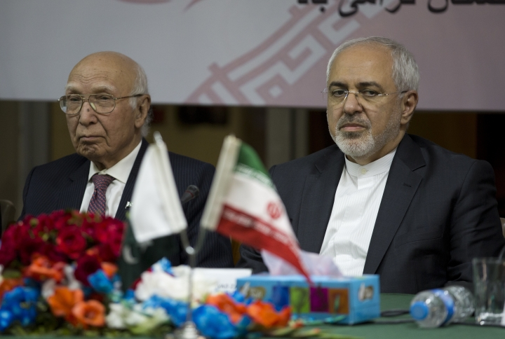 FILE - In this Monday, March 12, 2018 file photo, visiting Iranian Foreign Minister Mohammad Javad Zarif, right, attends a seminar with former Pakistani adviser on foreign affairs, Sartaj Aziz, at the Institute of Strategic Studies in Islamabad, Pakistan. Zarif wrapped up a trip to Pakistan in which he made a surprise offer to let Islamabad take part in a major port project partly funded by Pakistan's archrival India. (AP Photo/B.K. Bangash, File)