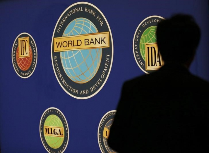 FILE PHOTO - A man is silhouetted against the logo of the World Bank at the main venue for the International Monetary Fund (IMF) and World Bank annual meeting in Tokyo October 10, 2012. REUTERS/Kim Kyung-Hoon