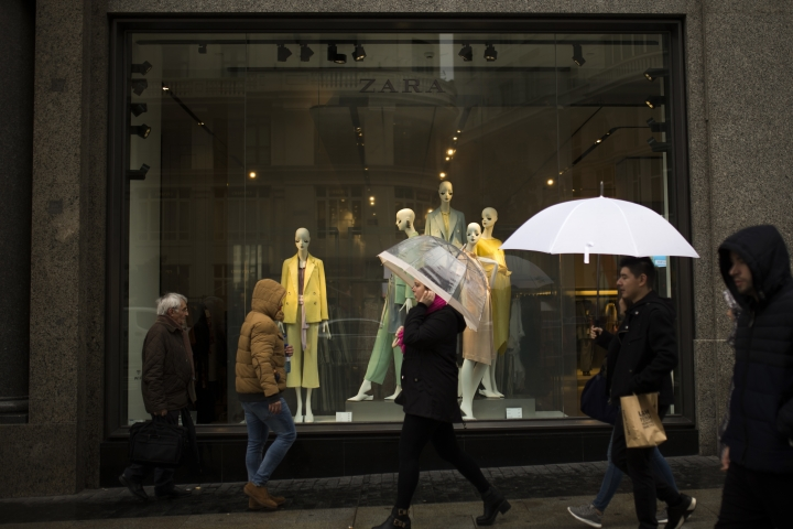 People walk past a display window of a Zara shop at the Gran Via avenue in Madrid, Wednesday, March 14, 2018. Zara fashion brand owner Inditex says strong sales and investment in technology for its online and physical stores boosted net profit in the past fiscal year by 7 percent. (AP Photo/Francisco Seco)