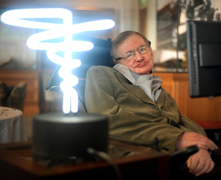 In this Feb. 25, 2012 photo, Professor Stephen Hawking poses beside a lamp titled 'black hole light' by inventor Mark Champkins, presented to him during his visit to the Science Museum in London. Hawking, whose brilliant mind ranged across time and space though his body was paralyzed by disease, died early Wednesday, March 18, 2018, a University of Cambridge spokesman said. He was 76. (Anthony Devlin/PA via AP)