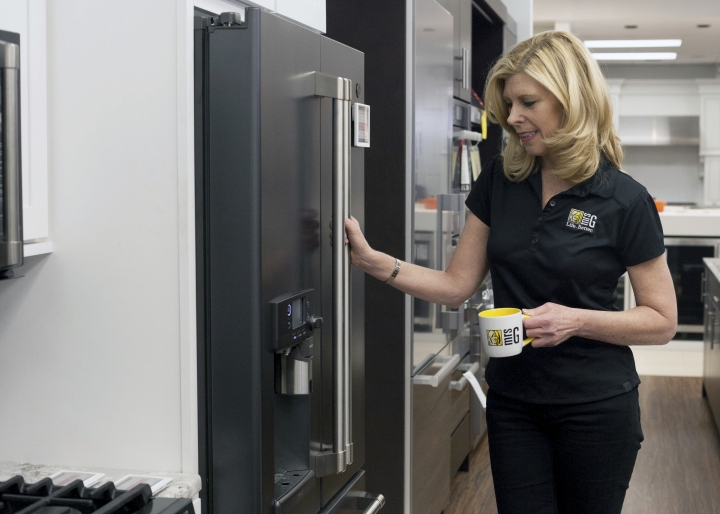 "In this March 11, 2018, photo provided by Mrs. G Inc., Debbie Schaeffer, owner of Mrs. G, an appliance retailer in Lawrence Township, N.J., poses for a photo at the GE Cafe Keurig Refrigerator display. A slowdown in home sales is creating opportunities for small businesses like home renovators and appliance dealers. ""People are confident and spending money and reinvesting in their homes,"" Schaeffer said. (Ashlee Cain/Mrs. G Inc. via AP)"