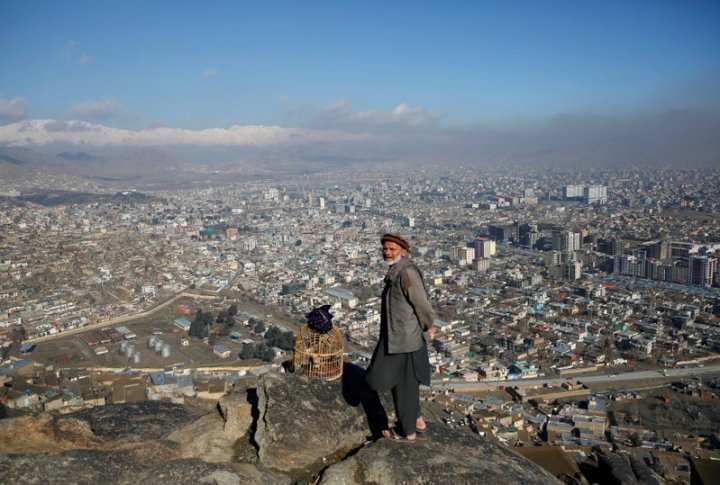 FILE PHOTO: An Afghan man stands beside a bird cage on a hilltop overlooking Kabul, Afghanistan February 27, 2018. REUTERS/Mohammad Ismail/File Photo