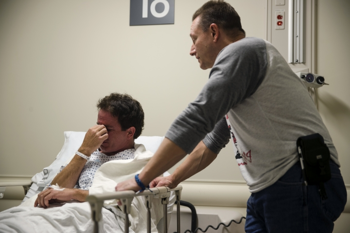 Patient Ryan Ciccozzi, left, waits with his brother-in-law Ron Grzechowiak before his surgery at the Hospital of the University of Pennsylvania in Philadelphia, Tuesday, Jan. 23, 2018. During Ciccozzi's surgery a fluorescent dye was used to find hidden cancer cells near his heart and in a lung. Researchers believe the use of fluorescent dyes, which make cancer cells glow to make them easier for surgeons to find, may give patients a better shot at survival. (AP Photo/Matt Rourke)