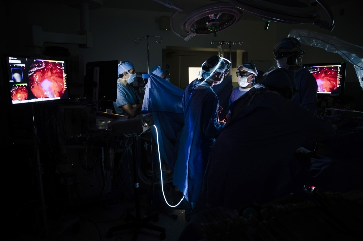 Dr. Sunil Singhal, center right, views a monitor to look at a tumor in his patient, made visible with the use of a special camera and fluorescent dye at the Hospital of the University of Pennsylvania in Philadelphia, Tuesday, Jan. 23, 2018. Researchers are testing fluorescent dyes that make cancer cells glow to make them easier for surgeons to find, giving patients a better shot at survival. (AP Photo/Matt Rourke)