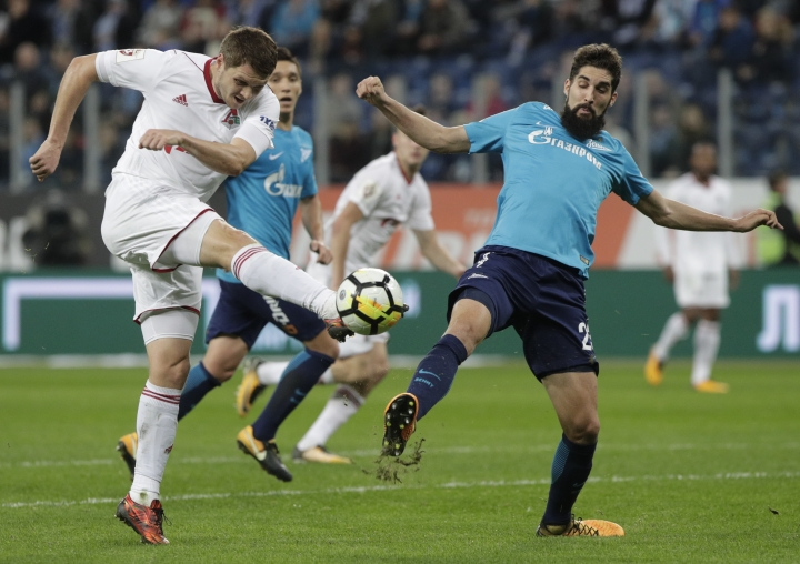 """FILE - This is a Sunday, Oct. 29, 2017 file photo of Lokomotiv's Ukrainian player Taras Mykhalyk, left, fights for the ball with Zenit's Miha Mevlja during a Russia's Premier League soccer match between Zenit St. Petersburg and Lokomotiv Moscow in St. Petersburg, Russia, The Ukrainian government Wednesday March 14, 2018 has ordered its athletes not to take part in any competitions held in neighboring Russia, which the country accuses of occupying its territory. The Ukrainian Youth and Sports Ministry issued a decree Wednesday to """"prohibit ... the participation of members of the Ukrainian national sports teams in any sports competitions held on the territory of the Russian Federation."""" (AP Photo/Dmitri Lovetsky/ File)"""
