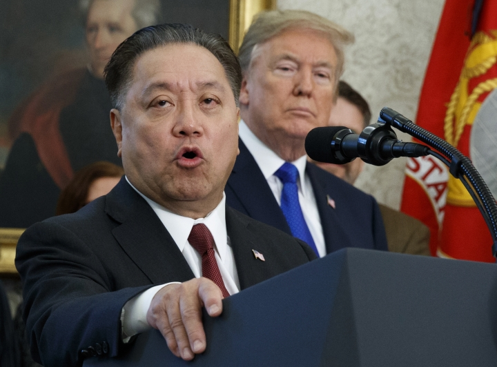 FILE - In this Thursday, Nov. 2, 2017, file photo, Broadcom CEO Hock Tan speaks while U.S. President Donald Trump listens, in background, during an event at the White House in Washington, to announce the company is moving its global headquarters to the United States. Broadcom says it's dropping its $117 billion buyout bid for rival chipmaker Qualcomm, following Trump's decision to scuttle the proposed combination due to national security concerns. (AP Photo/Evan Vucci, File)