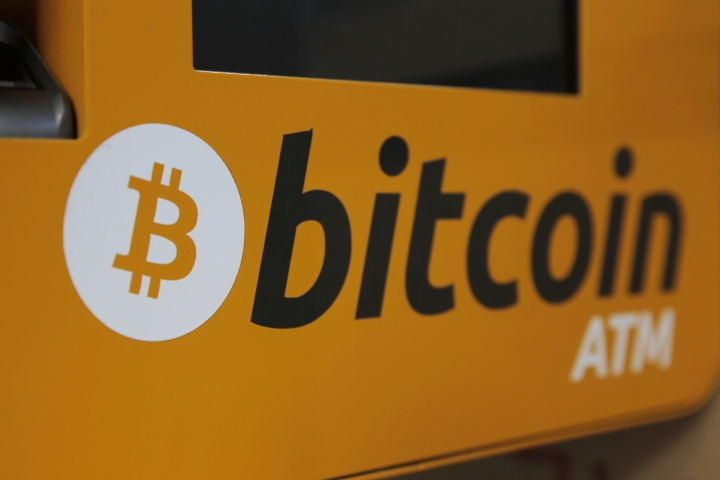 FILE- In this Dec. 21, 2017, file photo, a Bitcoin logo is shown is displayed on an ATM in Hong Kong. Google says it is going to ban advertisements for cryptocurrencies such as bitcoin, as well as related content like trading advice and cryptocurrency wallets. (AP Photo/Kin Cheung, File)