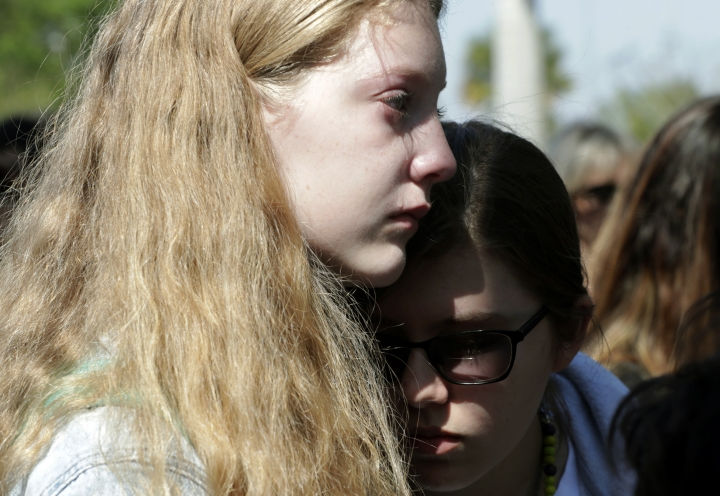 Hannah Grinbank, 13, left, cries as she and Morley Prager, right, listen to students speak at Pine Trails Park, as part of a nationwide protest against gun violence, Wednesday, March 14, 2018, in Parkland, Fla. Tens of thousands of young people in U.S. communities big and small walked out of school to demand action on gun violence Wednesday in the biggest demonstration yet of the student activism that has emerged since last month's massacre of 17 people at Marjory Stoneman Douglas High School. (AP Photo/Lynne Sladky)