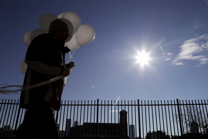 An administrator at James Ferris High School walks with 17 balloons prior to a student walkout to demand action on gun violence, Wednesday, March 14, 2018, in Jersey City, N.J. The 17 balloons represent each of the students who lost their life during a school shooting in Parkland, Fla., in February. (AP Photo/Julio Cortez)